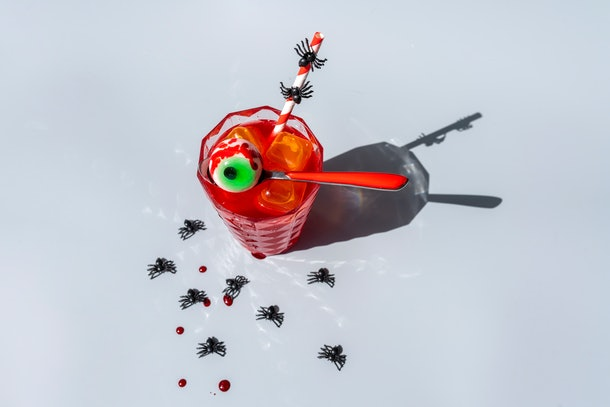 A Halloween cocktail sits on a countertop surrounded by plastic spiders.