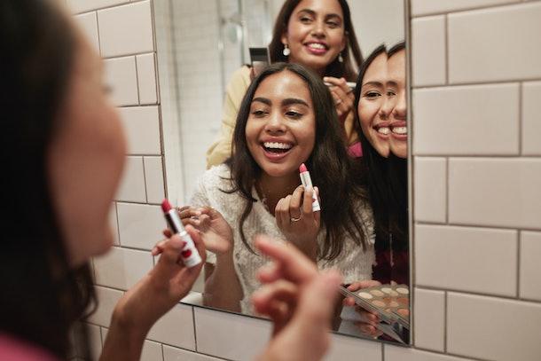 Three friends crowd around a bathroom mirror to apply lipstick.