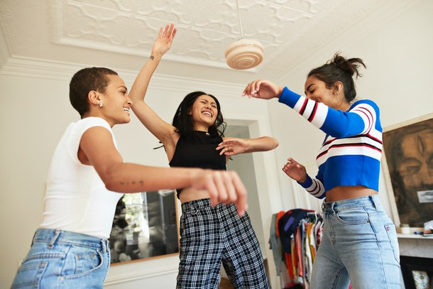 Three friends dance around in their bedroom at home.