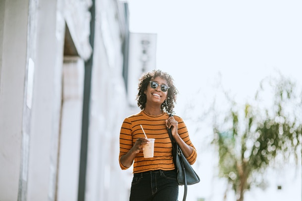 A happy woman in an orange shirt walks down the street with an iced coffee.