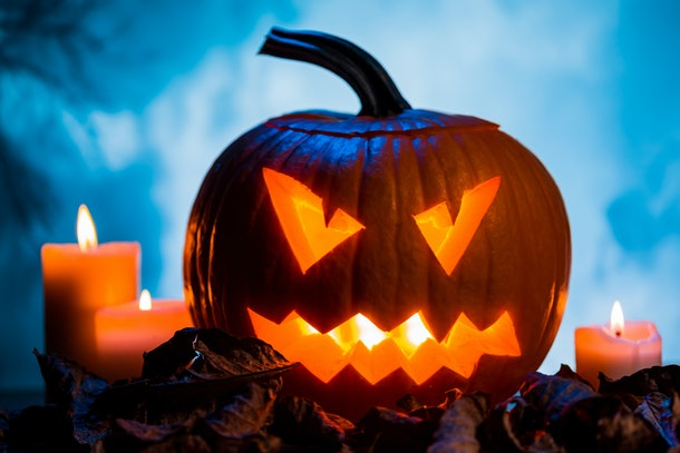 A jack-o'-lantern sits on a pile of leave next to a candle.