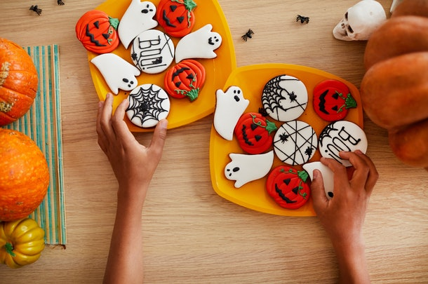 A woman's hands places Halloween cookies on a plate.