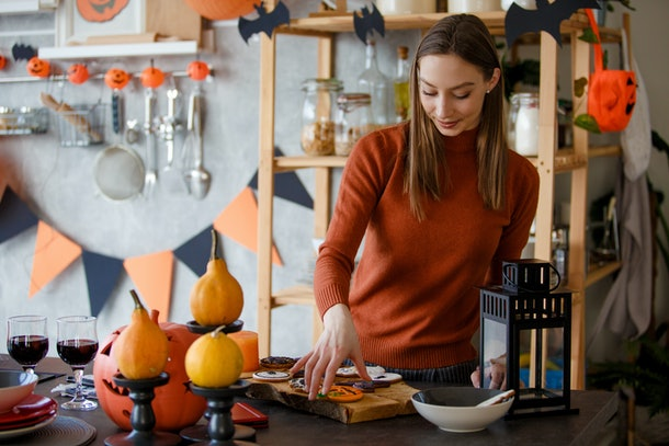 A woman arranges Halloween cookies on a board in her kitchen.