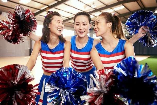 Three cheerleaders in their uniforms hang out in the gym.