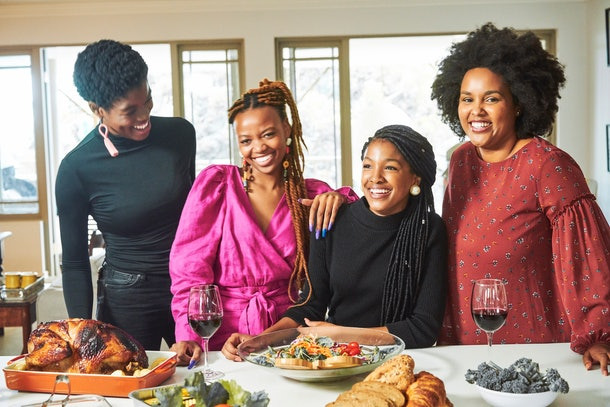 A group of happy friends poses behind a table that's set for a Thanksgiving dinner.