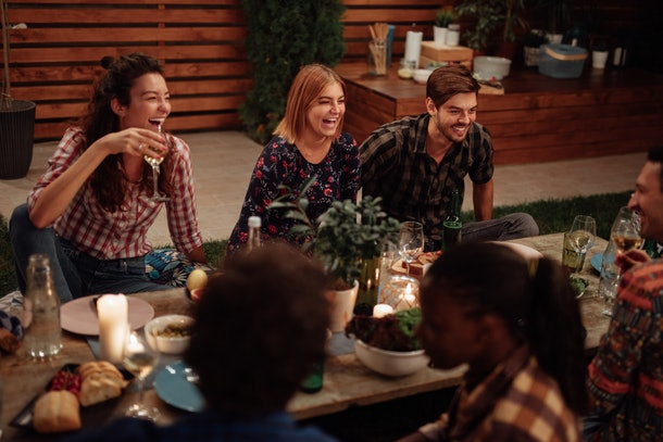 A group of happy friends enjoys a picnic meal in a backyard for Friendsgiving.