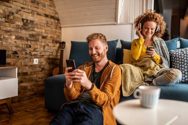 A happy couple relaxes at home while looking at their phones in a trendy living room.