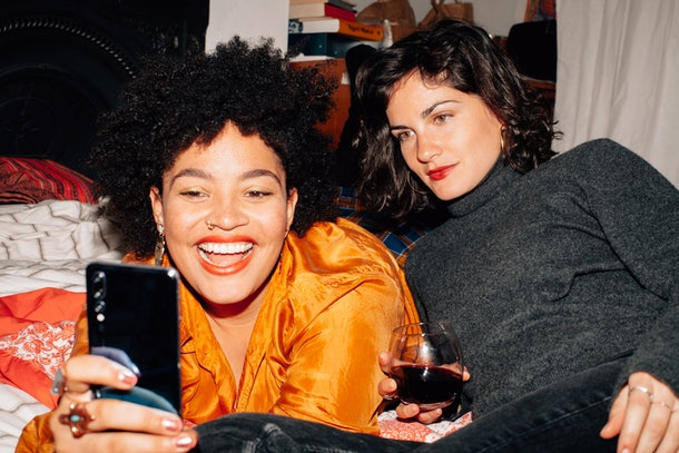 Two happy friends pose for a selfie with wine on a bed.