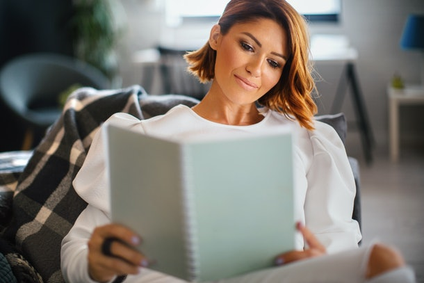 A trendy woman reads a book in a comfy chair in her bright apartment.