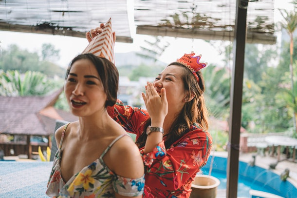 A girl places a birthday hat on her friend, while laughing.