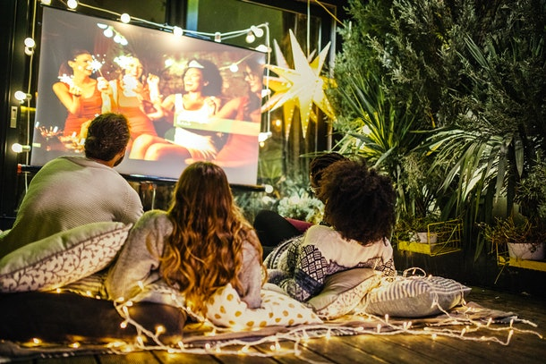 A group of friends watches a movie while sitting on pillows and blankets in their backyard movie theater setup.