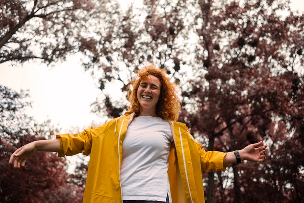A young woman with red hair and a yellow raincoat acts out something while playing charades in the fall.