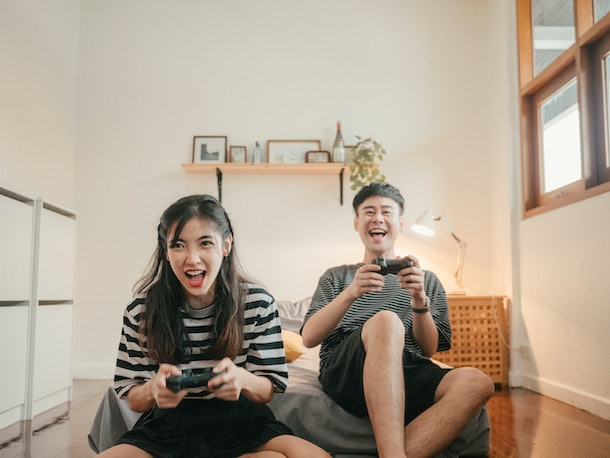 A young Asian couple laughs and gets competitive while playing video games at home.
