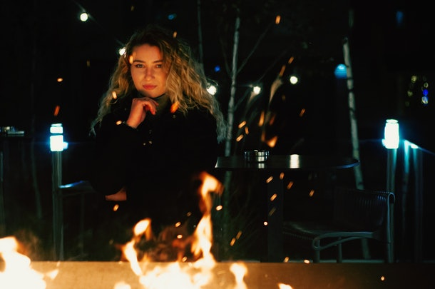 A young woman with blonde hair sits behind a fire pit as embers rise to the night sky.