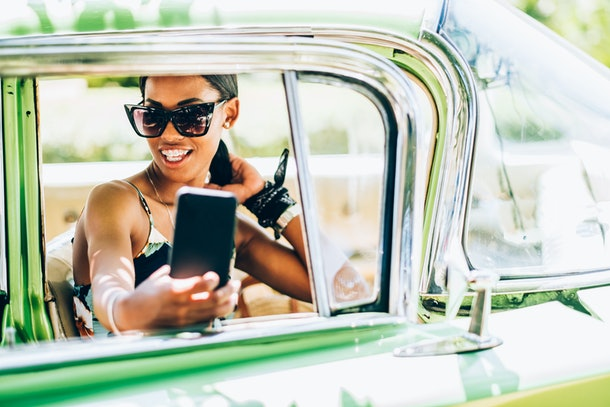 A fashionable woman in sunglasses snaps a selfie in a green vintage car on a sunny day.