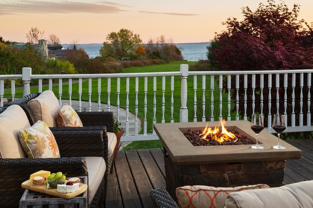 An outdoor fire pit has two couches next to it, in addition to a little table with a cheese board.