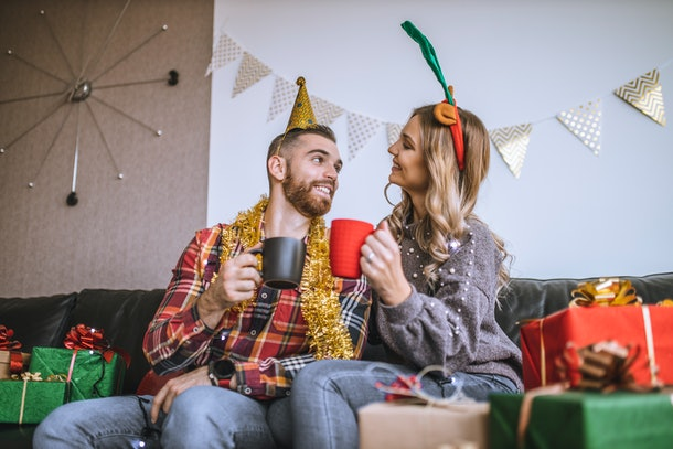 A happy couple toasts their Christmas mugs while surrounded by presents on Christmas morning.