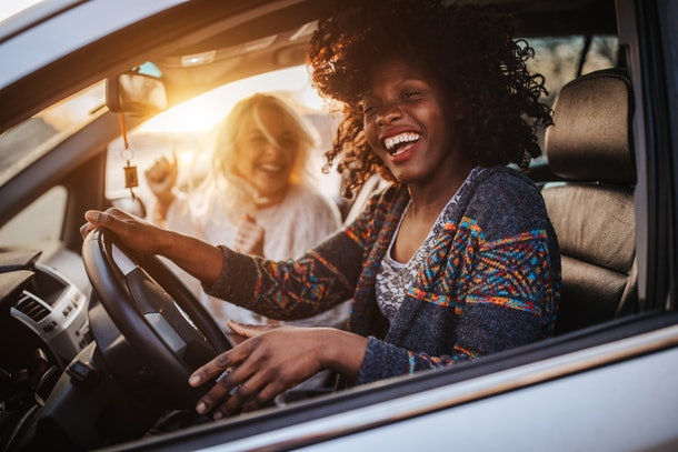 A young lesbian couple laughs while taking a scenic drive at sunset.