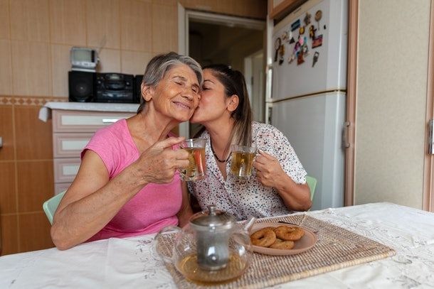 A daughter kisses her mom while they enjoy some afternoon tea at home.