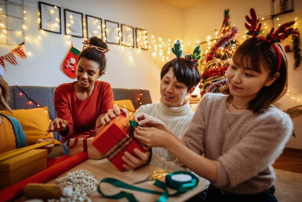 A group of friends wraps presents together while wearing holiday-themed outfits.