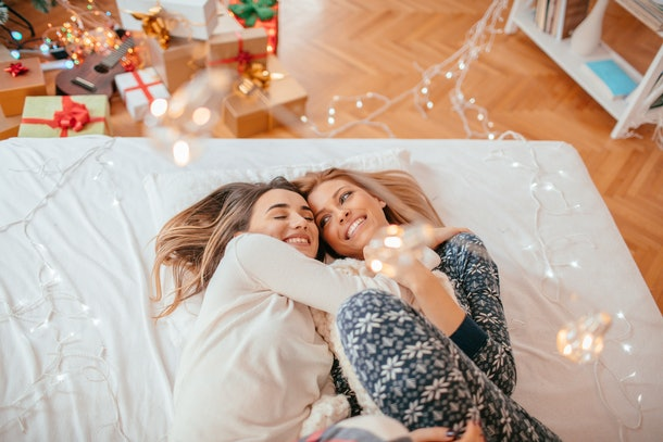 A lesbian couple lays in bed amongst twinkly lights and snuggles for a picture.