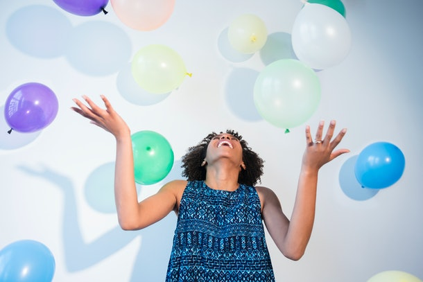 A happy woman admires balloons falling around her.