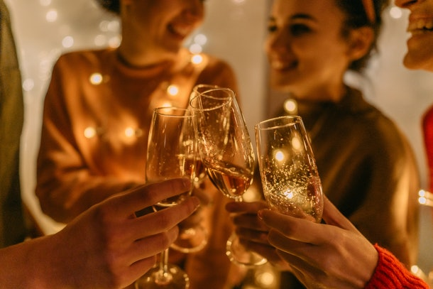 A group of friends cheers with champagne glasses at home.