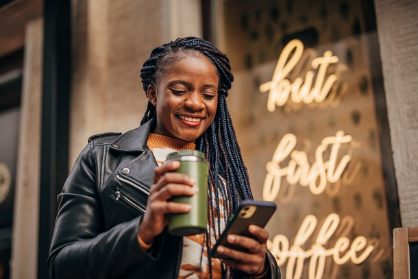 A happy woman in a leather jacket holds a to-go cup of coffee while texting.