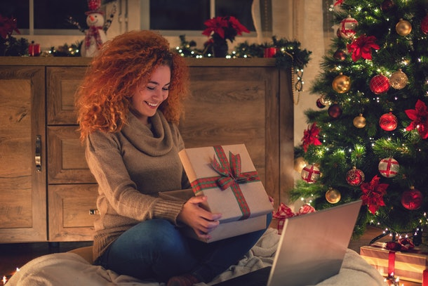 A happy woman opens up a Christmas present while on a virtual Secret Santa gift exchange.