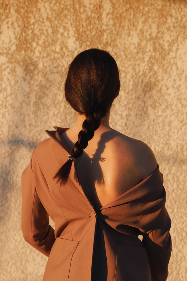 A young woman stands outside in a brown jacket with her hair in a single braid.