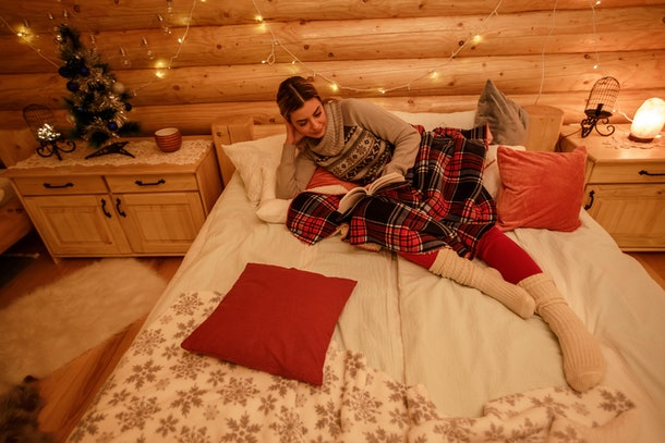 A girl in her Christmas pajamas lounges in bed while reading, laying next to her little Christmas tree and fairy lights