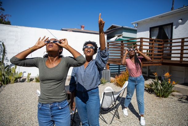 Three happy women gaze up at the solar eclipse in their solar eclipse glasses.