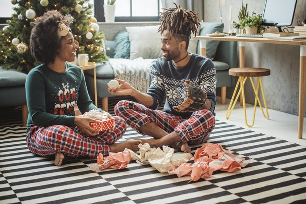 A happy couple wearing Christmas loungewear sits on the floor of their living room while opening presents.