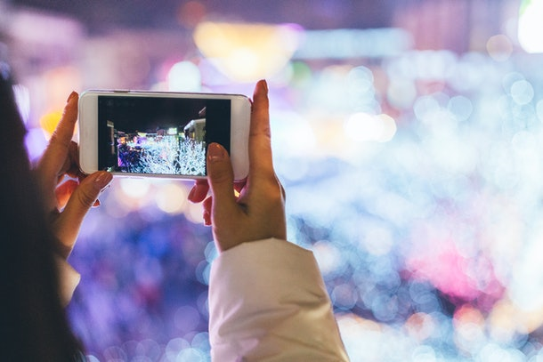 A young woman holds a phone up to take a picture of a drive-thru Christmas light show.