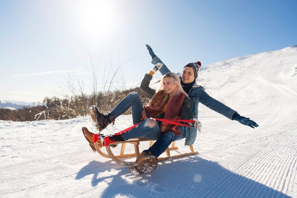 A man and woman sled down a slope, spreading their hands out as if flying down the hill.
