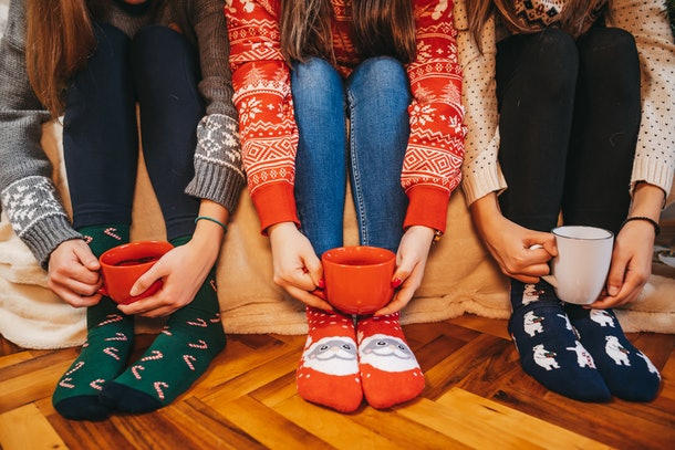 Three women wearing Christmas socks hold their festive mugs of hot chocolate.