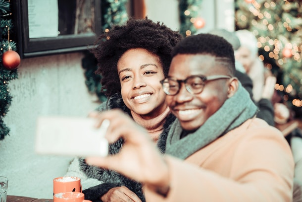A young Black couple has a photo shoot on a snow day with holiday decorations and drinks.