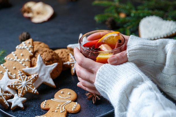 A woman holds a Christmas cocktail next to gingerbread cookies.