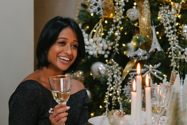 A woman in a gray sweater raises her champagne glass with a smile on her face to toast to a new year.
