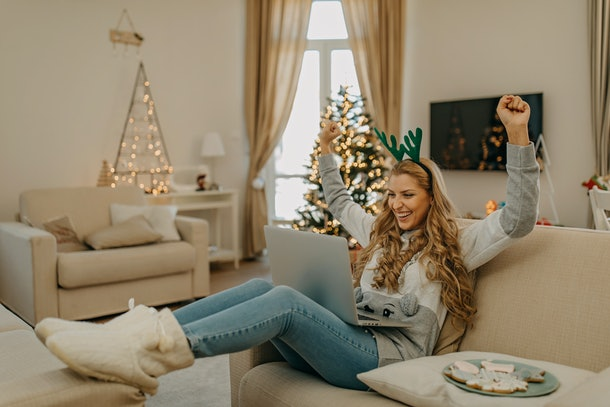 A woman on the couch, eating cookies and staying festive, raises her arms in celebration on her virtual Christmas party.