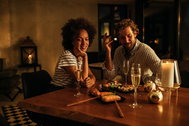 A trendy couple enjoys a sushi dinner and champagne on New Year's Eve in their home.