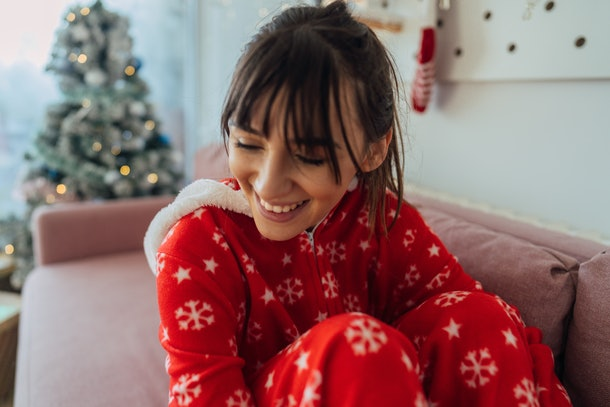 A happy woman wearing holiday pajamas sits on her couch next to her Christmas tree.