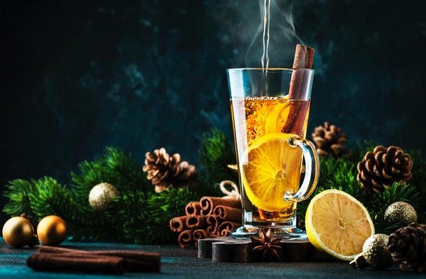 Hot water is poured into a hot toddy glass with lemon slices and a cinnamon stick, while sitting next to holiday garland and pine cones.