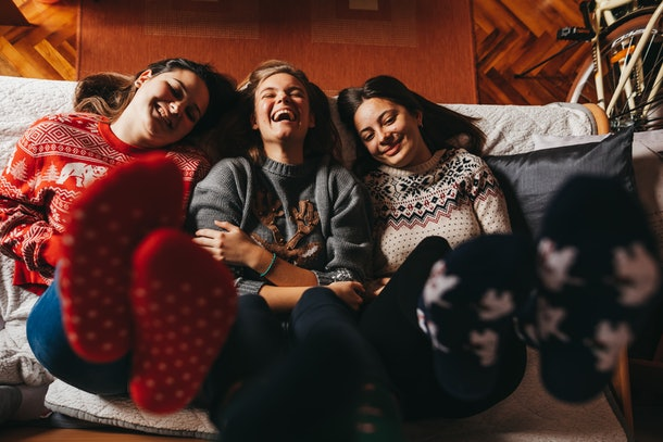 Three roommates relax on a bed while wearing cozy winter socks.