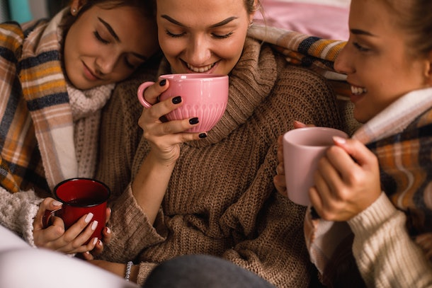 Three friends wearing sweaters, cuddle close while sipping on hot chocolate.
