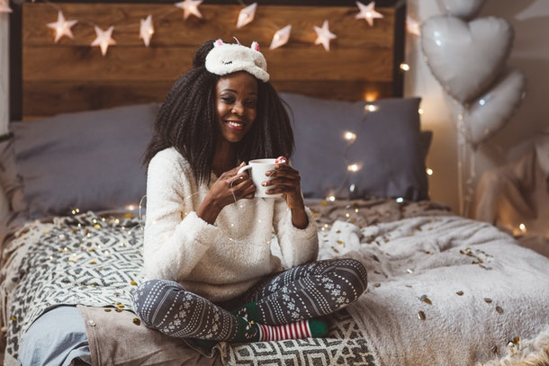A happy woman in festive pjs holds a coffee mug on her bed with string lights in the background.
