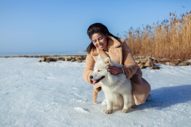 A happy woman in a pea coat poses with her white husky in the snow on a sunny day.