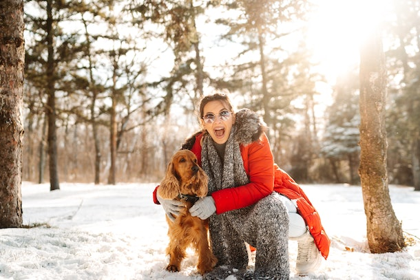 A happy woman in a red winter coat poses with her dog in the snow.