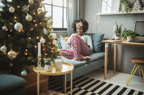 A cozy woman in her festive PJs lounges on the couch.