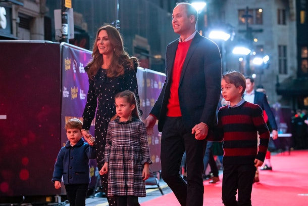 Prince William, Kate, and their children walk hand in hand on the red carpet.